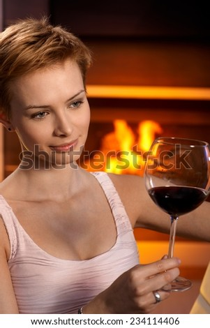 Daydreaming woman looking at glass of wine sitting by fireplace. - stock photo