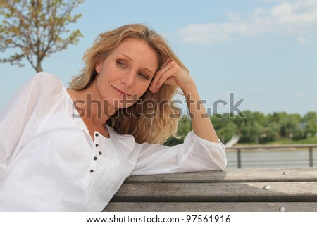 Daydreaming woman on a park bench