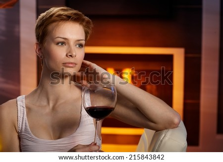 Daydreaming woman sitting in cosy room by fireplace, holding a glass of wine, daydreaming. - stock photo