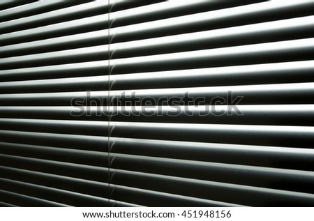 Daylight coming through closed metallic blinds, high-contrast abstract pattern.