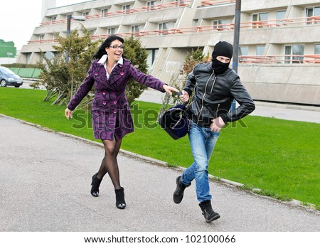 Daylight robbery on the street. Thief steals a bag. - stock photo