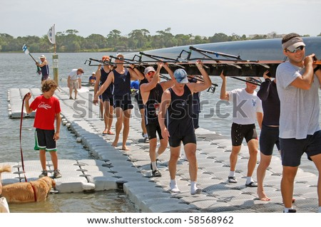"DAYTONA BEACH, FL - JULY 24:  A boy and his dog watch as the men's team bring in their boat during the  ""Halifax Rowing Association's Summer Regatta 2010"" on July 24, 2010 in Daytona Beach, Florida. - stock photo"