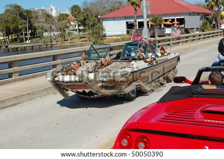"DAYTONA BEACH, FL - MARCH 6:  A bizarre boat/car is driven over the Main Street bridge during ""Bike Week 2010"" in Daytona Beach, Florida. - stock photo"