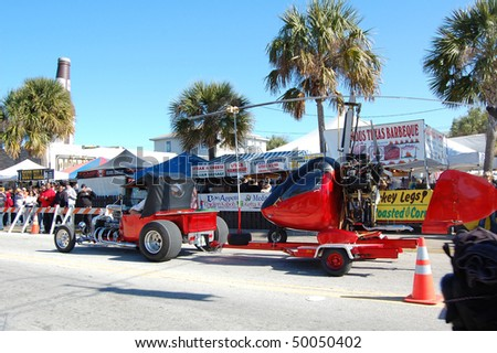 "DAYTONA BEACH, FL - MARCH 6:  A custom car and matching helicopter cruise down Main Street during ""Bike Week 2010"" in Daytona Beach, Florida."