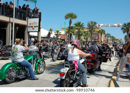"DAYTONA BEACH, FL - MARCH 17:  Bikers cruise Main Street on St. Patrick's Day during ""Bike Week 2012"" in Daytona Beach, Florida. - stock photo"