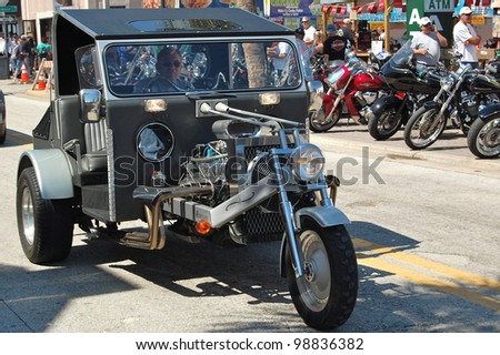 "DAYTONA BEACH, FL - MARCH 17:  Customized motorcycles cruise Main Street during ""Bike Week 2012"" in Daytona Beach, Florida. - stock photo"