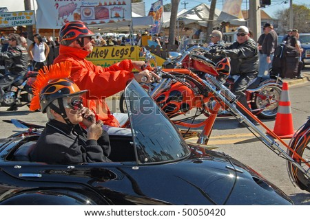 "DAYTONA BEACH, FL - MARCH 6: Older biker couple cruising down Main Street while woman talks on cell phone during ""Bike Week 2010"" in Daytona Beach, Florida. - stock photo"