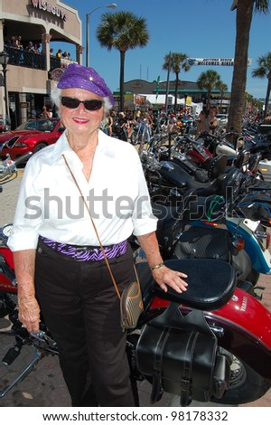 "DAYTONA BEACH, FL - MARCH 17:  Spectators of all ages dress up to cruise Main Street amid the sea of bikers in town for ""Bike Week 2012"" in Daytona Beach, Florida. March 17, 2012 - stock photo"