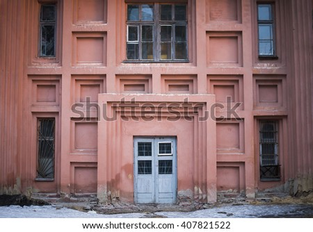 de focused background of old red house wall with wooden door and window. Exterior and Front Door of a Beautiful Old House. Facade of an old house - stock photo
