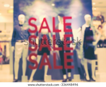 """De focused/Blur image of boutique window with dressed mannequins. Boutique display window with mannequins in fashionable dresses. Words """"sale"""" on boutique display window. Retro effect. - stock photo"""