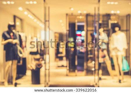 De focused/Blur image of boutique window with dressed mannequins. Boutique display window with mannequins in fashionable dresses. Vintage effect.. - stock photo