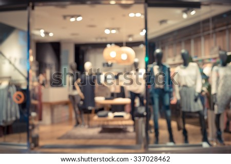 De focused/Blur image of boutique window with fashionable dresses and bags. Toned image. - stock photo
