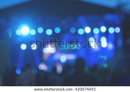 De-focused / blurred concert crowd silhouettes enjoying the music. - stock photo