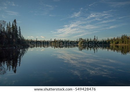 Dead calm lake in early morning with reflections of conifers and wispy cirrus clouds