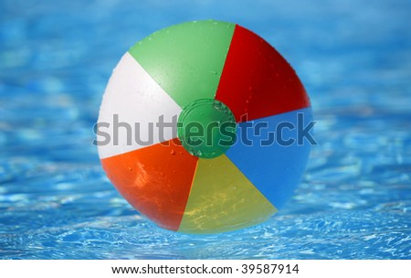 Dead centred shot from a low angle of a floating beachball in a bright blue pool - stock photo