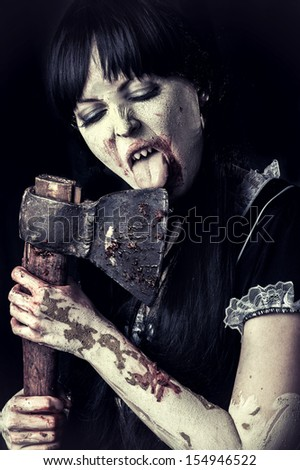 Dead female zombie licking bloody axe. Halloween concept.  - stock photo