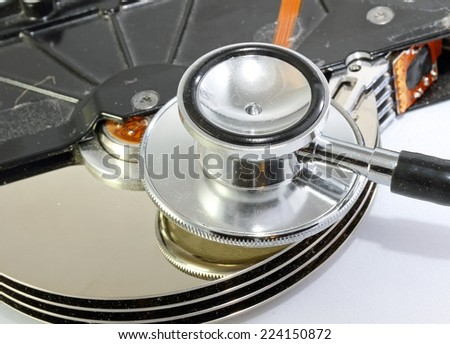 dead hard disk infected with computer virus with syringe and stethoscope - stock photo