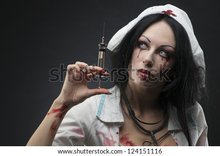 Dead nurse holding syringe with blood - stock photo