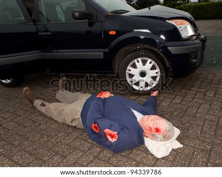 Dead or unconscious man lying next to a wrecked car - stock photo