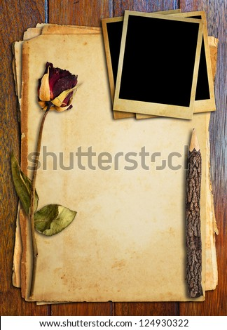 Dead roses, old pencil and old photo put on old paper. - stock photo