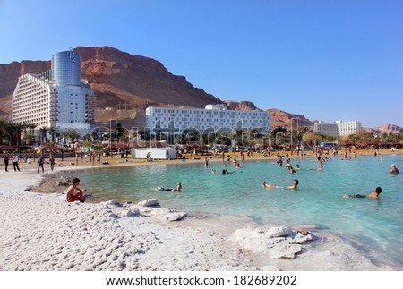 Dead Sea, Ein Bokek, Israel - February 18: vacationers and tourists bathe in the Dead Sea on the background of luxury hotels, on February 18, 2014 in Ein Bokek, Dead Sea, Israel - stock photo