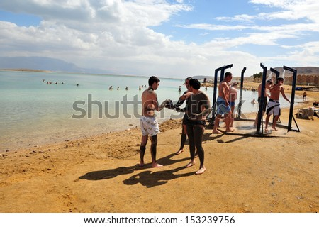 DEAD SEA, ISR - MAR 18:Young people in a bathing suit enjoys natural mineral mud on March  18 2010.The Dead Sea is filled with minerals including calcium, iodine, saline, potassium, and bromide. - stock photo