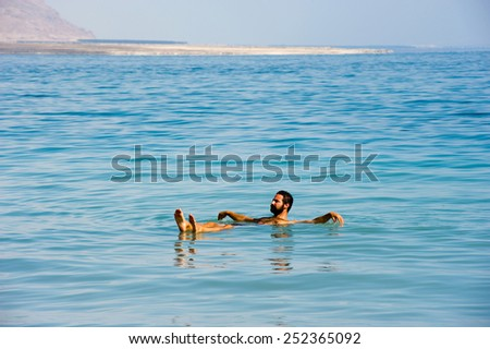 DEAD SEA; ISRAEL - 16 OCTOBER, 2014: A man floating in the salty water of the dead sea in Israel - stock photo