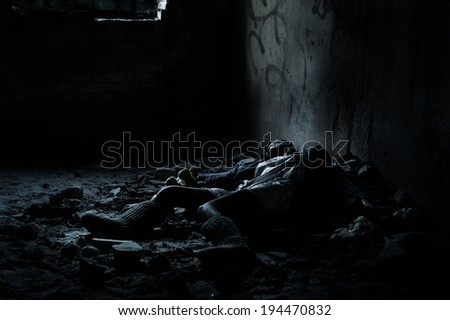 Dead woman lying on the dirty floor in a heap of rubbish in the basement - stock photo