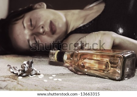dead woman lying on the floor, bottle of whiskey in her hand  and pills - stock photo