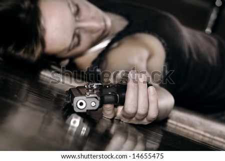 dead woman lying on the floor, gun in the hand - stock photo