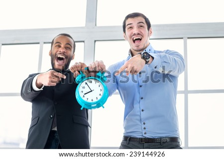 Deadline and late for work. Businessmen are holding big clock alarm clock while young people point fingers at his watch and shout directly into the camera. - stock photo