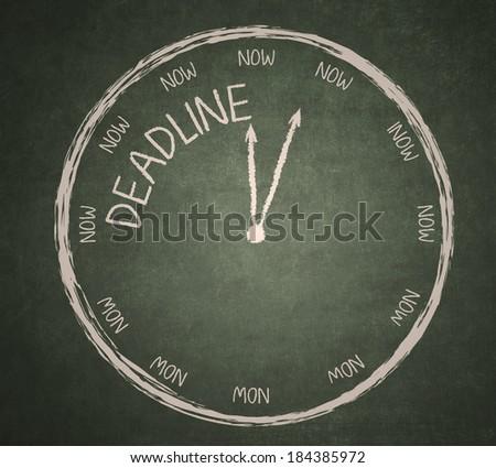 Deadline writing and a clock on a blackboard - stock photo