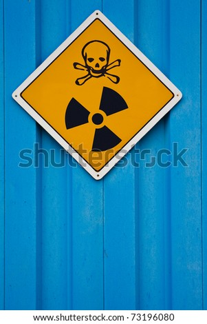 Deadly nuclear radiation warning sign with skull and crossbones on blue background. - stock photo