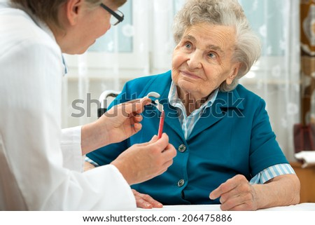 Deaf senior woman during a hearing test - stock photo