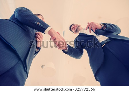 Deal and handshaking business partners. Two Confident businessman shake hands with each other in the business office view from below - stock photo