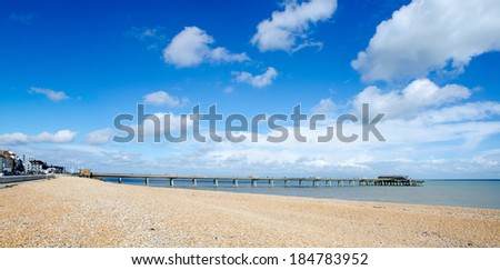 DEAL, KENT, UK - MAR 23, 2014.  The Beach and Pier at Deal, set against a beautiful blue sky with white clouds.  The pier was completed in 1957, replacing an earlier pier damaged during WW2. - stock photo