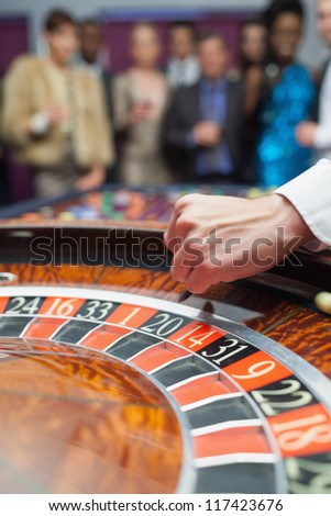 Dealer dropping ball into roulette wheel in casino - stock photo
