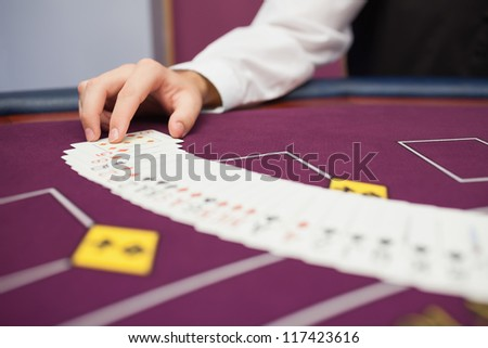 Dealer spreading the deck at poker game in casino - stock photo