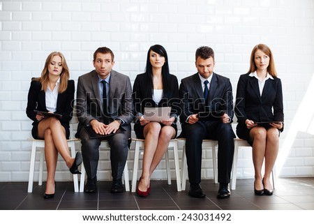 Dealing with job interview. Group of business people waiting for interview