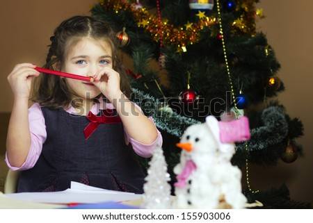 Dear Santa ... Beautiful little girl writes letter to Santa Claus in festively decorated room  - stock photo