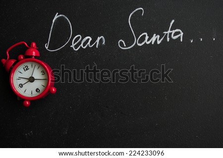 Dear Santa is written on a blackboard and christmas decoration