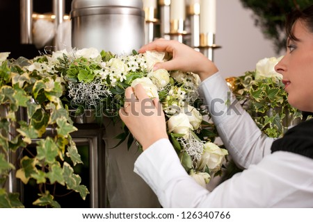 death and dolor  - mortician on funeral with urn preparing the flowers - stock photo