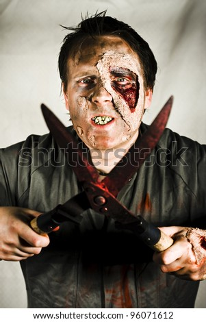 Death By Zombie. An evil decaying zombie holding a pair of bloodied garden shears with blades open. - stock photo