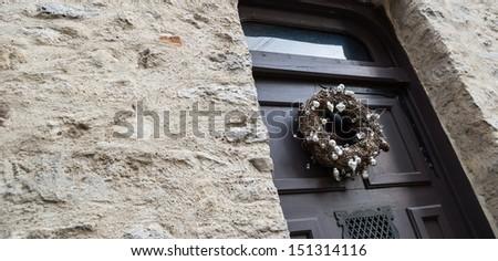 Death concept. Faded Christmas wreath on a house door. - stock photo