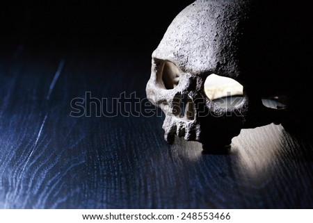 Death concept. Glowing human skull on dark background with free space for text - stock photo