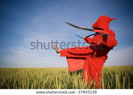 Death-like person with scythe performs a kick! - stock photo