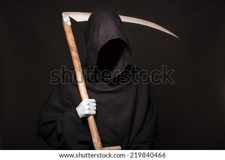 Death reaper over black background. Halloween. Studio portrait on black background - stock photo