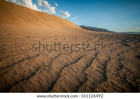 Death Valley sand dune looks like a big wave - stock photo