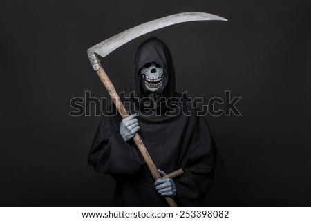 Death with scythe standing in the dark. Halloween . Studio portrait on black background - stock photo