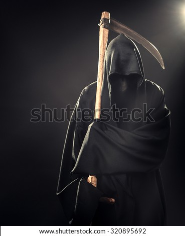 death with scythe standing in the fog at night - stock photo